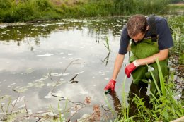 Man with waders and gloves on taking a sample from a pond